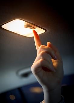 Primo piano della donna che accende la luce nel salone dell'auto