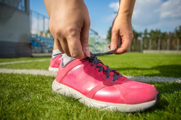 Foto del primo piano della donna che lega le scarpe da ginnastica rosa sul campo di calcio soccer