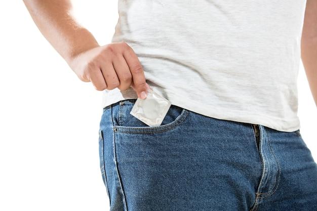 Primo piano del giovane che mette il preservativo nella tasca dei jeans jeans