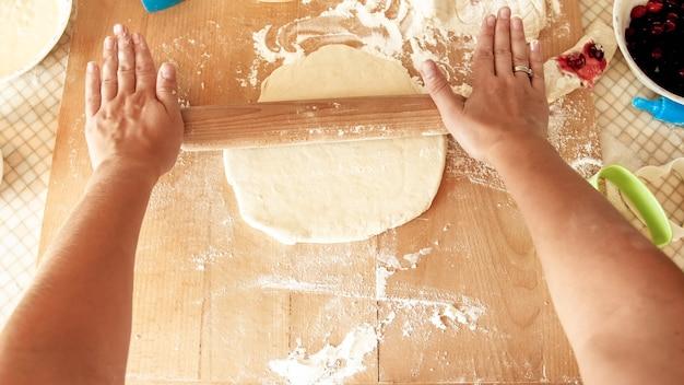 Primo piano della giovane donna che fa l'impasto per la pizza