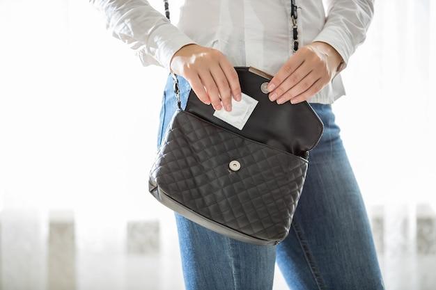 Primo piano di una giovane donna che tira fuori il preservativo dalla borsetta