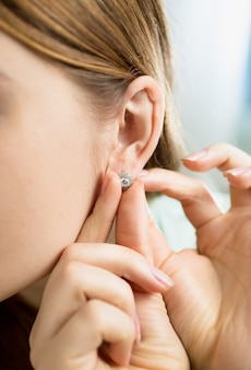 Foto del primo piano della giovane donna che indossa l'erring con il diamante