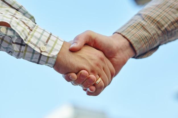 Maschera del primo piano degli uomini d'affari che agitano le mani, facendo un accordo