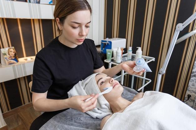 Maschera del primo piano del cosmetologo che fa maschera crema ad una ragazza adorabile in un salone di bellezza.