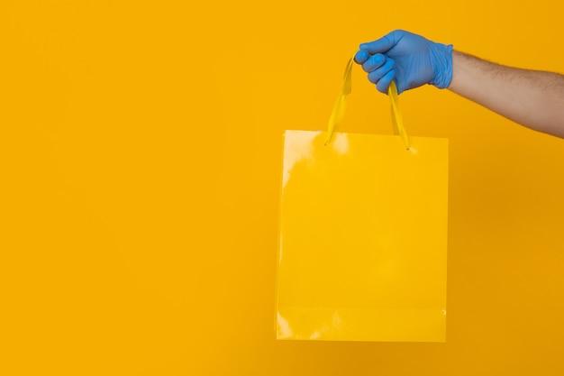 Maschera del primo piano del concetto di consegna. mano in guanti blu che tengono grande borsa colorata isolata sopra i precedenti gialli.