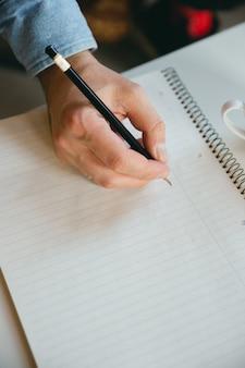 Maschera del primo piano di una scrittura della mano con una matita su un taccuino in bianco.