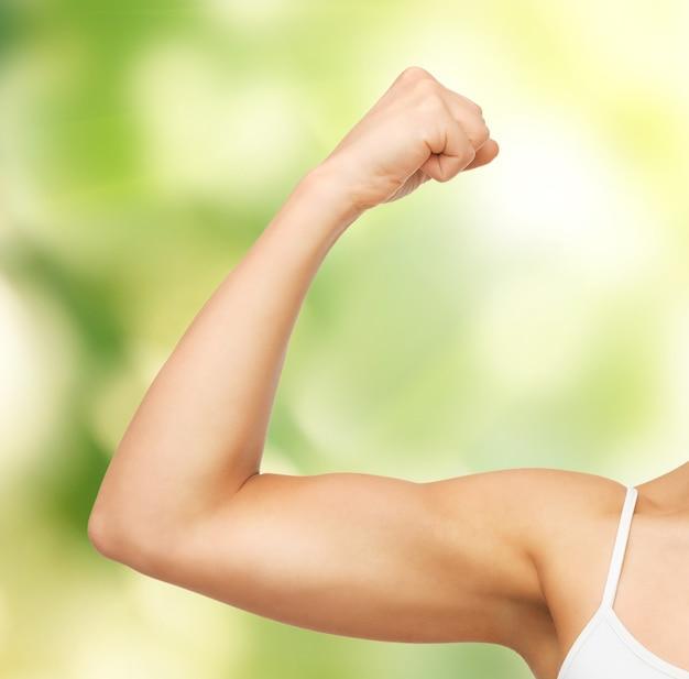 Foto in primo piano di una donna sportiva che flette i suoi bicipiti
