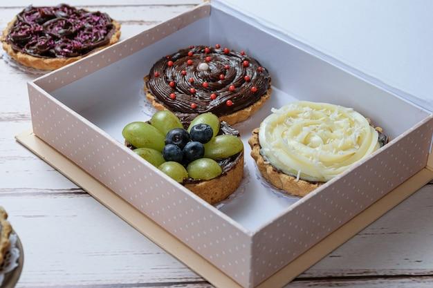 Primo piano di torta con pasta burrosa farcita con ganache al cioccolato, decorata con uva verde e mirtilli. all'interno di una confezione regalo e con altre torte.