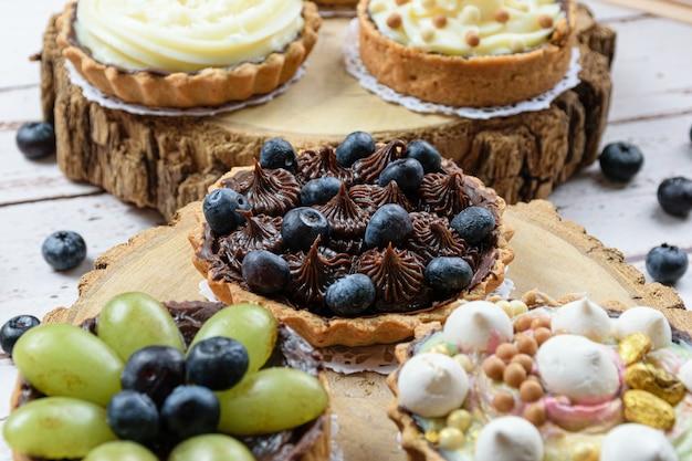 Primo piano di torta con pasta burrosa farcita con ganache al cioccolato, decorata con mertilos. su un piatto di legno e circondato da altre torte (vista laterale).