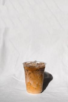 Tazza di plastica del primo piano di caffè freddo con latte sul tavolo