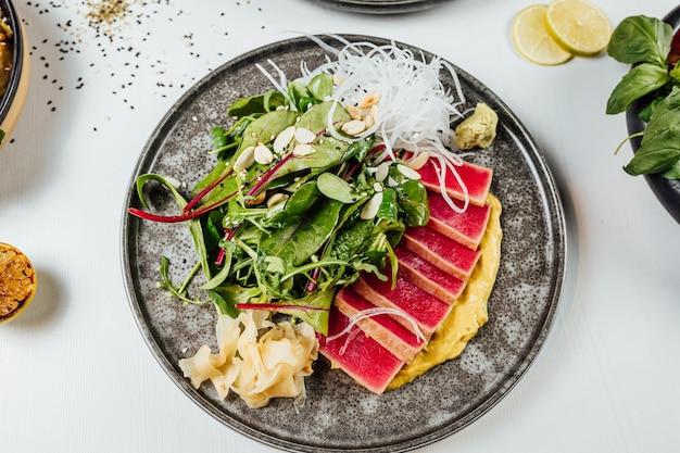 Primo piano di un piatto di sushi con verdure fresche sul tavolo bianco
