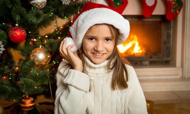 Ritratto del primo piano di una ragazza di 10 anni con un cappello da babbo natale seduto accanto al camino e un albero di natale decorato