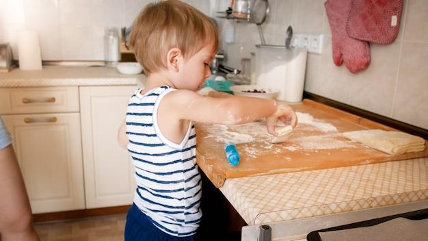 Ritratto del primo piano di adorabile bambino di 3 anni che cuoce i biscotti e rotola la pasta con il mattarello di legno. piccolo chef cuoco