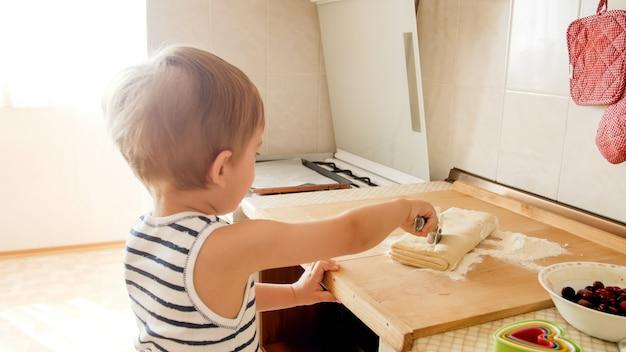Ritratto del primo piano di un adorabile bambino di 3 anni che cuoce i biscotti e arrotola la pasta con il mattarello