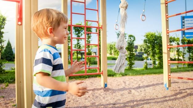 Ritratto del primo piano del ragazzino felice sorridente adorabile sul campo da giuoco dei bambini al parco