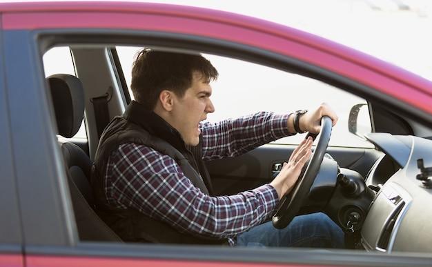 Ritratto del primo piano dell'autista maschio aggressivo che suona il clacson nell'ingorgo stradale