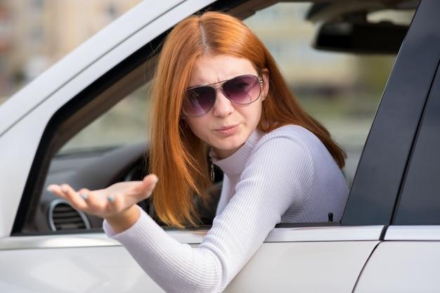 Ritratto del primo piano della donna arrabbiata che conduce un'automobile che grida a qualcuno con la mano su.