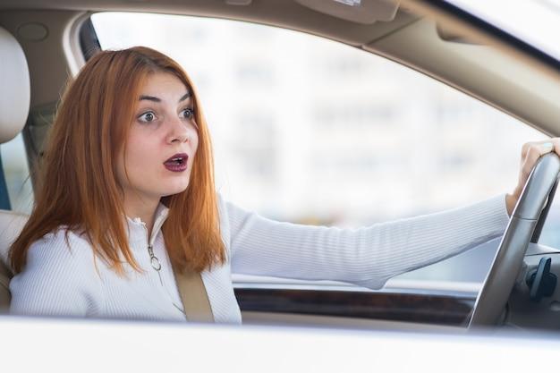Ritratto del primo piano della donna arrabbiata che conduce un'automobile che grida a qualcuno.
