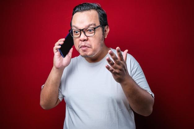 Closeup ritratto arrabbiato giovane uomo asiatico, tipo studente pazzo, incazzato dipendente gridando mentre sul telefono isolato sfondo rosso. emozione umana negativa espressione del viso sentimento atteggiamento