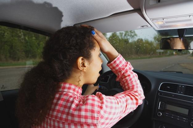 Ritratto del primo piano, giovane donna seduta arrabbiata incazzata dai conducenti di fronte a lei, mano sulla testa, fondo isolato della via della città. concetto di ingorgo stradale di rabbia