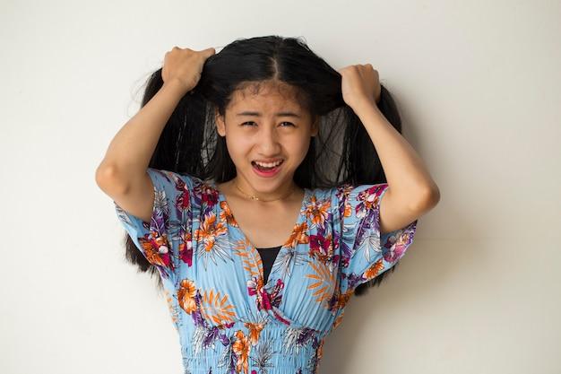 Ritratto del primo piano della giovane donna asiatica che graffia la testa con la mano