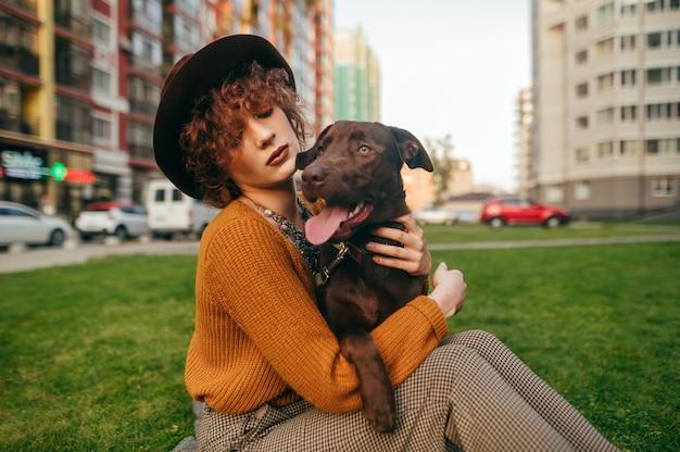 Closeup ritratto di una ragazza attraente che indossa un cappello con un cane in mano