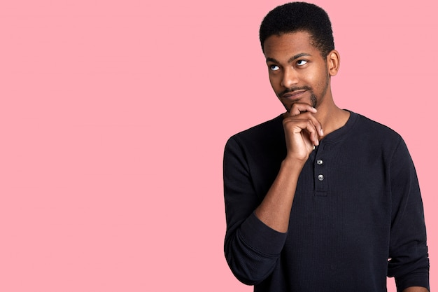 Ritratto del primo piano del tipo africano premuroso attraente. il giovane uomo bello osserva da parte, tiene la mano sul mento e pensa al suo sogno, isolato su rosa. copia spazio per la tua pubblicità.