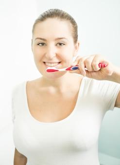 Ritratto del primo piano di bella donna castana che lava i denti