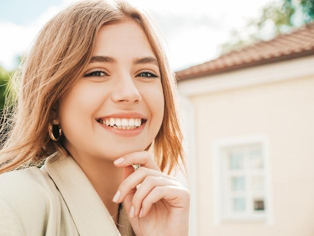Ritratto del primo piano di bella modella bionda sorridente. donna alla moda in posa in strada al tramonto. bella e allegra