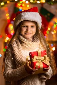 Ritratto del primo piano di bella ragazza sorridente che tiene il contenitore di regalo alla vigilia di natale