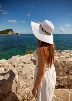Ritratto del primo piano di bella donna in cappello bianco che esamina mare