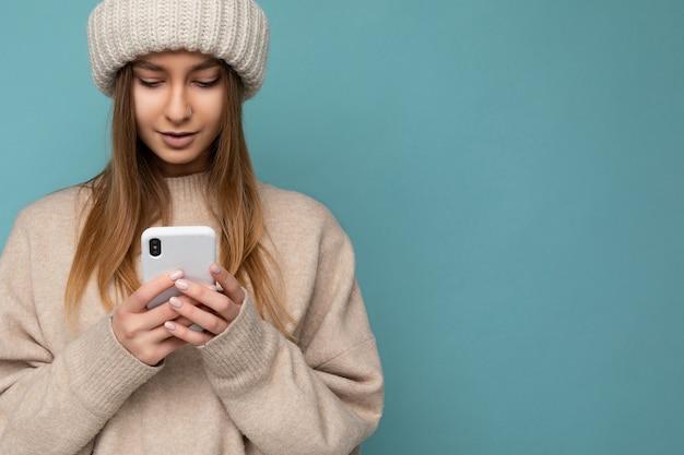Ritratto del primo piano bella giovane donna bionda che indossa un maglione caldo beige alla moda e