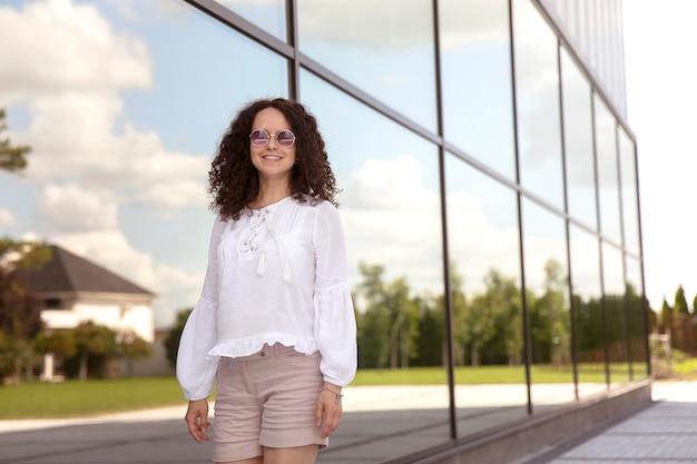 Ritratto del primo piano di bella giovane donna felice in occhiali da sole.