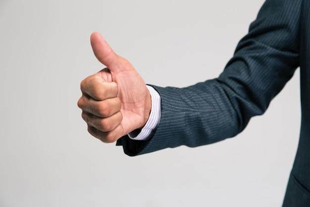 Ritratto del primo piano della mano dell'uomo d'affari che mostra pollice su isolato