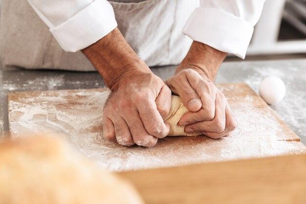 Closeup ritratto di maschio caucasico mani mescolando pasta per pasticceria, sul tavolo al forno o in cucina