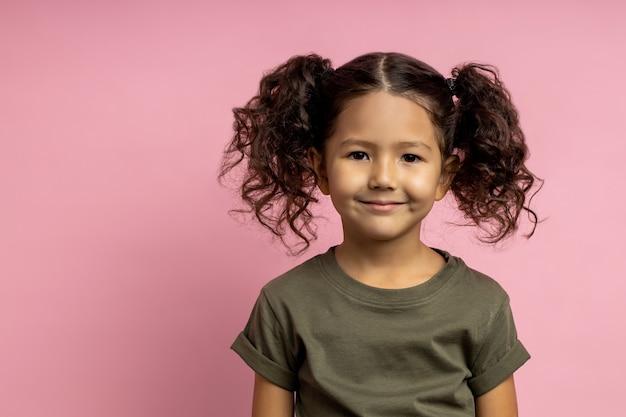 Ritratto del primo piano della piccola ragazza caucasica con l'acconciatura divertente, pelle marrone, maglietta cachi da portare, sorridente che sembra isolato. bambini, espressioni, emozioni.