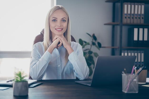 Il ritratto del primo piano della ragazza professionale allegra si siede sul posto di lavoro