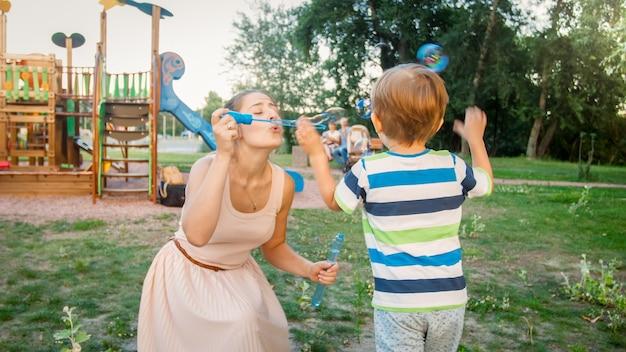 Ritratto del primo piano di un bambino allegro che cattura bolle di sapone colorate che sua madre sta soffiando nel parco