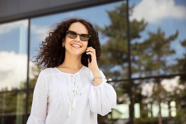 Closeup ritratto di una giovane donna allegra con i capelli ricci, parlando al cellulare, contro un edificio con sfondo della finestra. vista orizzontale.