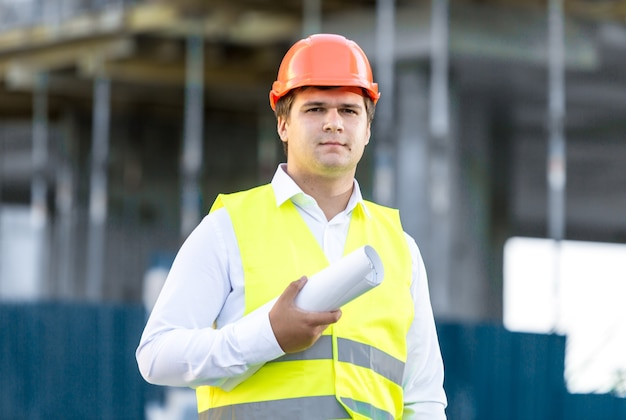 Ritratto del primo piano del direttore della costruzione che posa contro l'impalcatura