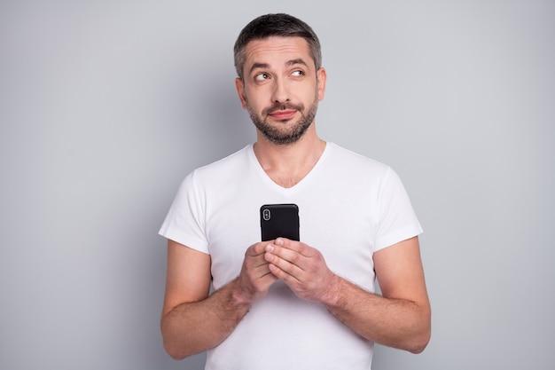 Il ritratto del primo piano del ragazzo creativo curioso che usa il telefono pensa alle idee