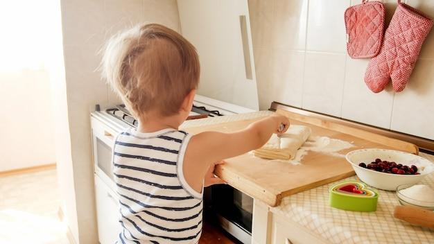 Ritratto del primo piano del ragazzo sveglio del bambino di 3 anni in piedi sulla cucina e la cottura della pasta. bambino che cucina e prepara la colazione