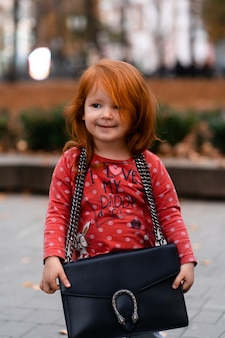 Ritratto del primo piano del bambino caucasico della ragazza dai capelli rossi sorridente adorabile sveglio che sta con la grande borsa della mamma nel parco di caduta di autunno fuori, guardando nella macchina fotografica, concetto di infanzia felice di stile di vita