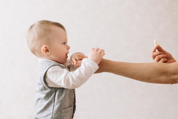 Ritratto del primo piano del neonato sveglio con le mani tese isolate su fondo leggero. il bambino tende il mais, che è nelle mani della mamma