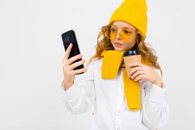 Ritratto del primo piano di una ragazza adolescente caucasica carina in un cappello invernale e sciarpa con un telefono in mano e un bicchiere di carta prendendo un selfie su bianco