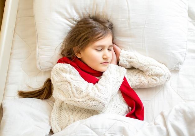 Ritratto del primo piano della ragazza sveglia in sciarpa e maglione che dorme a letto