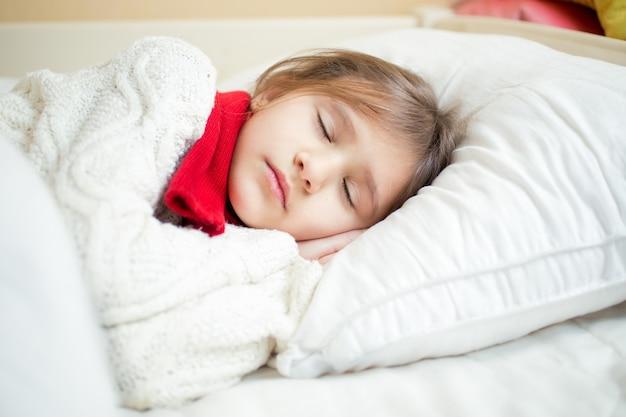 Ritratto del primo piano della ragazza sveglia in maglione e sciarpa che si trova sul cuscino bianco