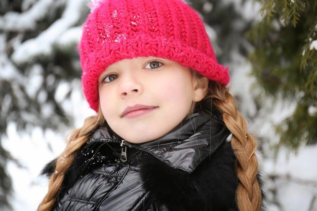 Ritratto del primo piano della bambina sveglia all'aperto in inverno