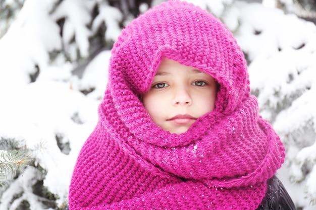Ritratto del primo piano della bambina sveglia che indossa lo snood lavorato a maglia caldo all'aperto