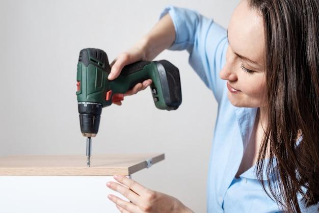 Closeup ritratto di una donna europea con un cacciavite in mano, raccoglie mobili